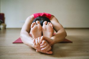 female performing yoga pose on wooden floor