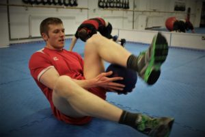 male performing abdominal exercises with medicine ball on the floor of the focus fitness centre in elgin, moray